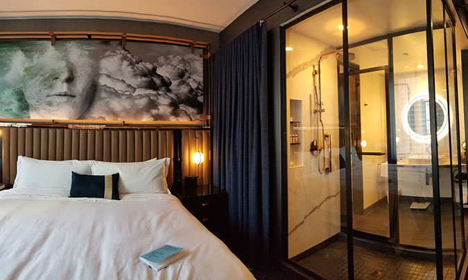 Hotel room bed with artwork hanging above it and right next door a full view of the shower and bathroom separated by glass shower doors