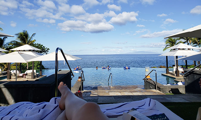A pair of female legs stretched out over a towel and lounger with an infinity pool and ocean view