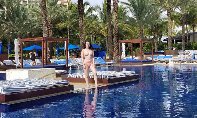 Geeves posing in pink bikini by a large blue pool between to lounge beds outside surrounded by palm trees