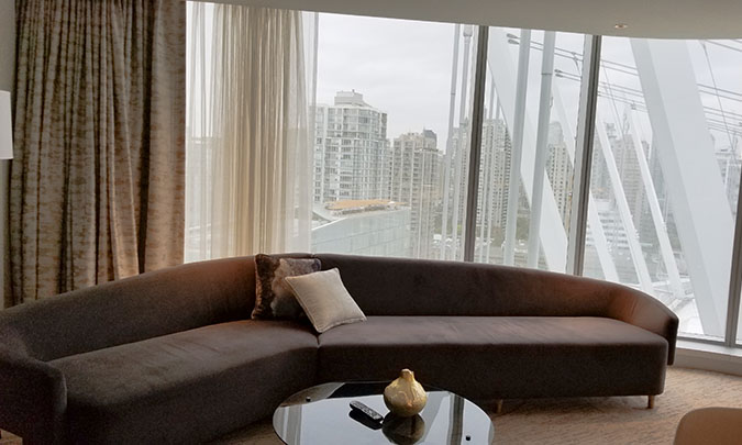 Long brown couch against a span of windows looking out onto the city of Vancouver at Marriott Hotel