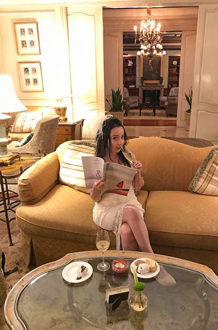 Geeves sitting on the couch in the club room at the Ritz, enjoying and sipping champagne and holding a magazine