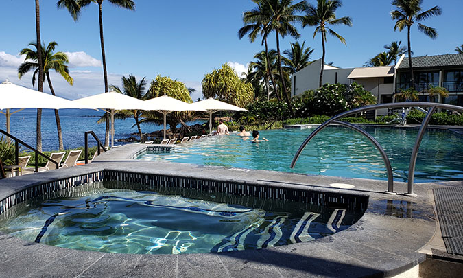 Modern pool and jacuzzi in front of the ocean, surrounded by palm trees and beach umbrellas