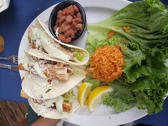 a plate of fish tacos, rice and beans