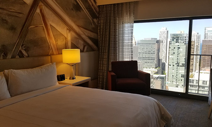 an inside of a hotel room with the view of downtown chicago