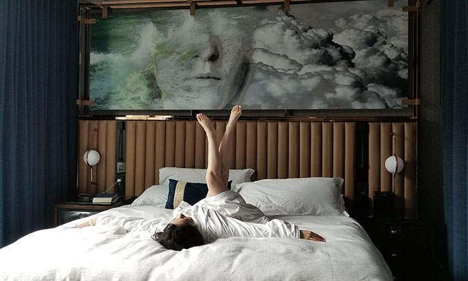 Geeves on a hotel room bed, in a robe with legs playfully up in the air