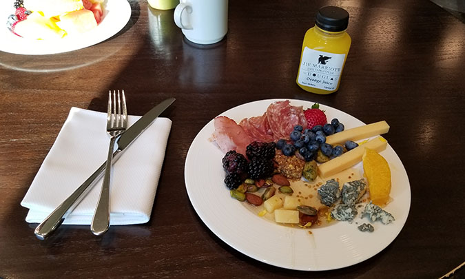 a mixed plate of fruit, cheese, and cold cuts