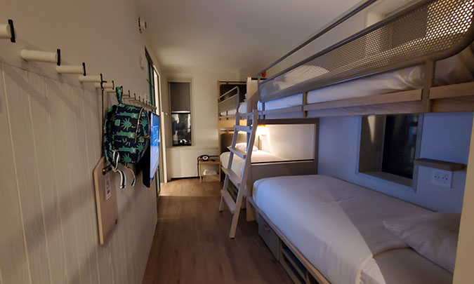 A narrow hotel room with bunk beds