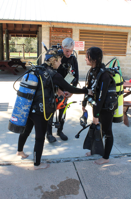 3 scuba divers in gear performing buddy checks