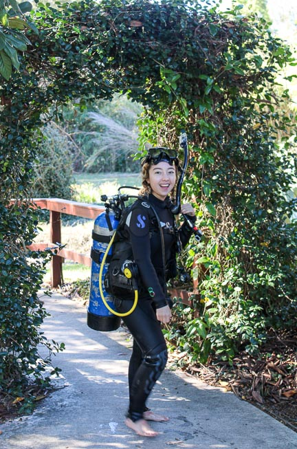 Geeves in scuba gear posing and standing under a ivy archway