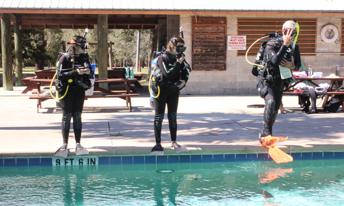 3 scuba divers ready to plunge into a swimming pool for training