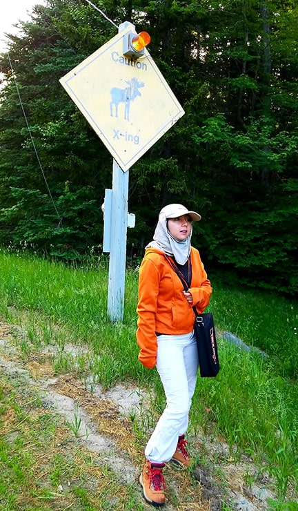 Geeves wearing a orange jacket and standing under a moose sign in Maine