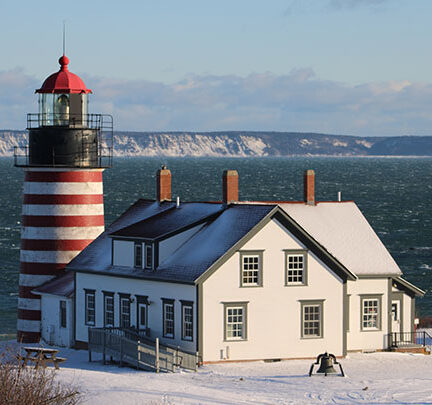 Full view of West Quodd Lighthouse, the lighthouse is red and white striped