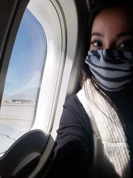 Geeves wearing a mask looking out the window of a plane