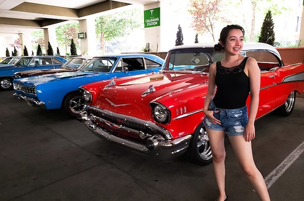 geeves posing in front of old classic cars