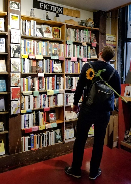 Man looking at a shelf full of books in Left Bank Books