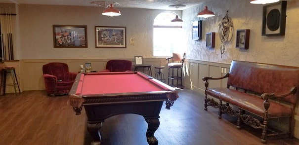 room with red pool table, antique leather love seat and photos on the wall