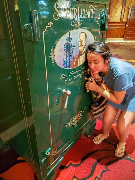Girl listening closely with her ear up against a green vault from silver legacy