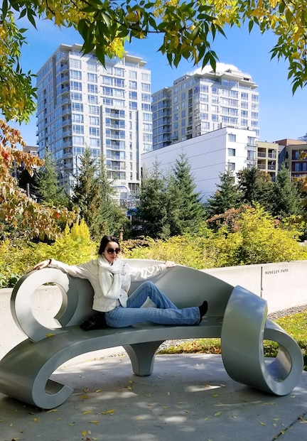 Geeves sitting and relaxing on a park bench with sky rise buildings behind her
