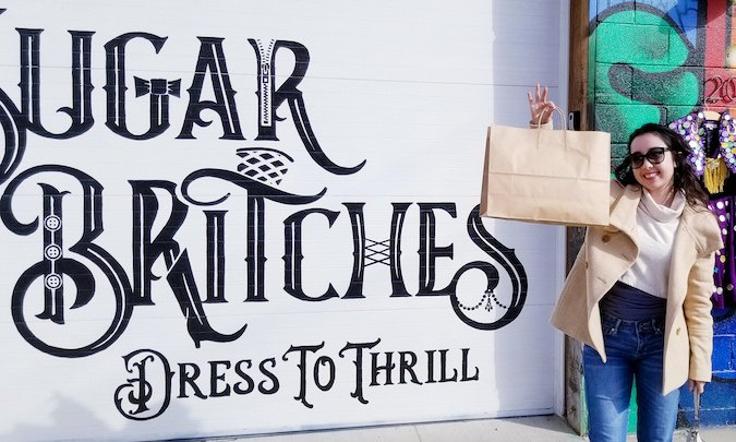 geeves holding a shopping bag outside of Sugar Britches mural