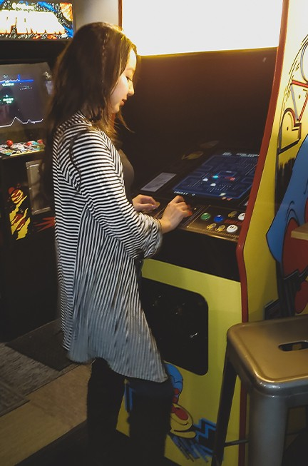 geeves playing pacman at the arcade in asheville