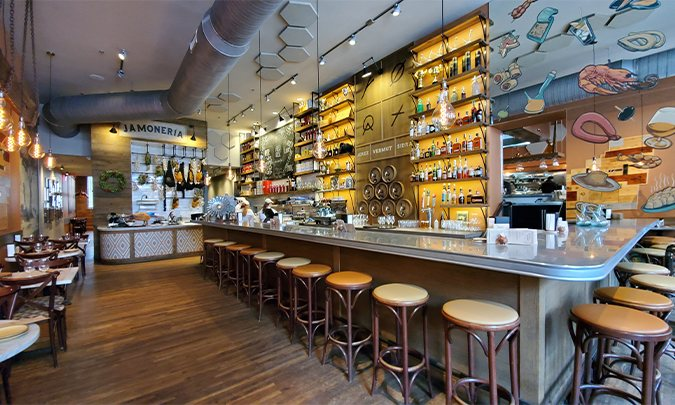 inside curate, a long bar with a counter and stool and at the end a jamoneria