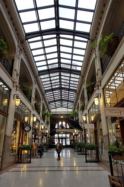long view of inside mall with glass ceiling and row of boutique shops