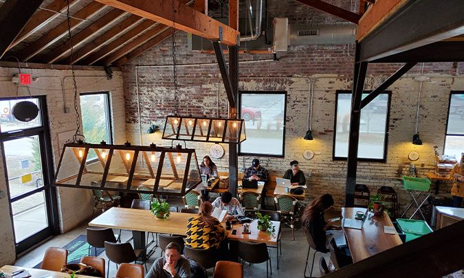 Inside of Summit Coffee, patrons sitting at tables on their laptops with coffee