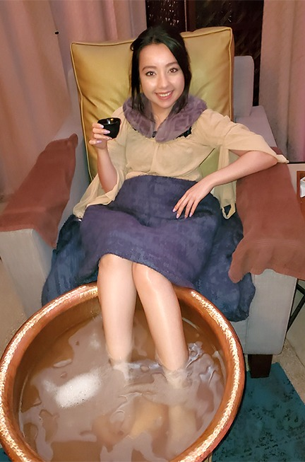 geeves with her foot in a round pedicure bowl and holding a cup of tea
