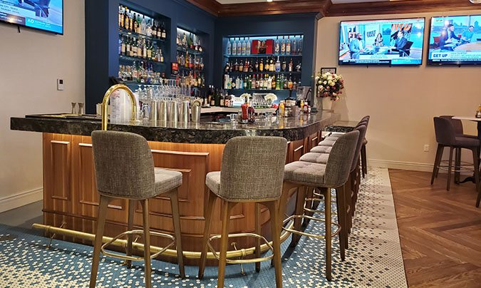 corner bar with bar stools and wall of bottled alcohol