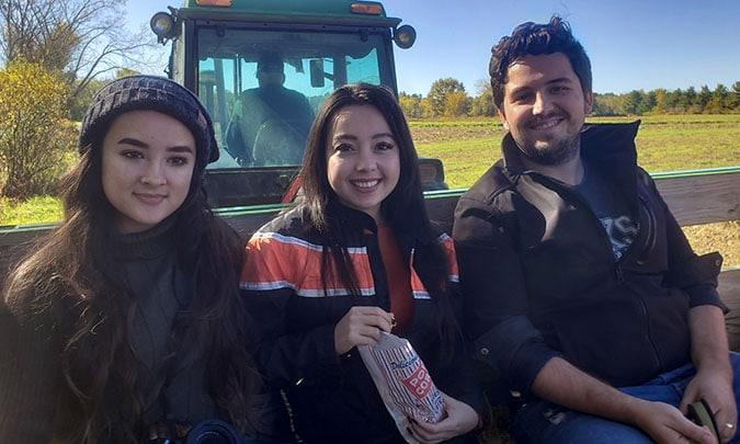 friends sitting in the back of tractor