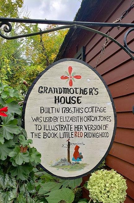 A sign that reads, Grandmother's house, built in 1786, this cottage was used by Elizabith Orton Jones to illustrate her version of the book little red riding hood