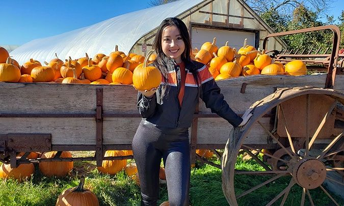 geeves holding a small pumpkin with a wagon full of pumpkins behind her.